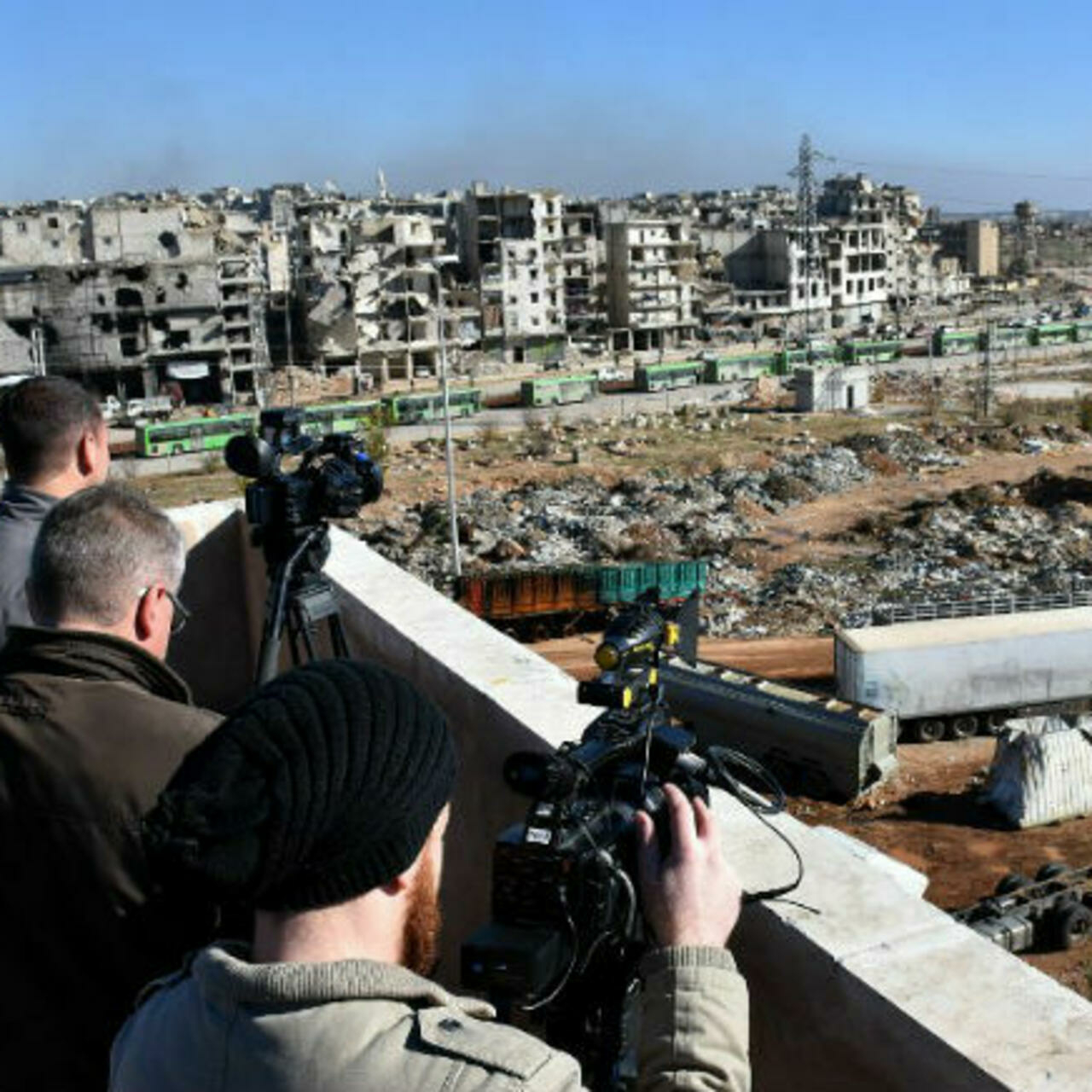 Journalists filming buses evacuating opposition fighters and their families from opposition-held neighborhoods in the besieged city of Aleppo - 15 December 2016 (George Ourfalian, AFP)