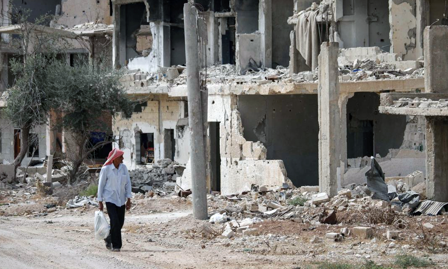 Syrian man passing near the rubble of buildings in a neighborhood controlled by the Syrian armed opposition in Daraa city, south of Syria - 2 October 2018 (AFP/Muhammad Abazaid)
