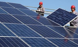 Two technicians installing solar power panels in one of the Syrian cities (Reuters)