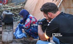 A journalist filming a displaced woman at the al-Sikka camp in Harbanoush town – 18 September 2021 (Enab Baladi – Iyad Abdul Jawad)