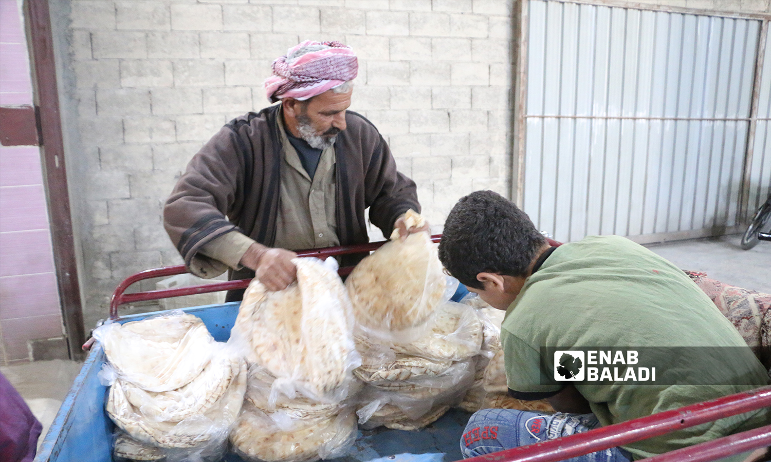 A man arranging bread pundles inside a small truck to transfer them to the selling center in al-Bab city - 8 October 2021 (Enab Baladi - Siraj Mohammed)