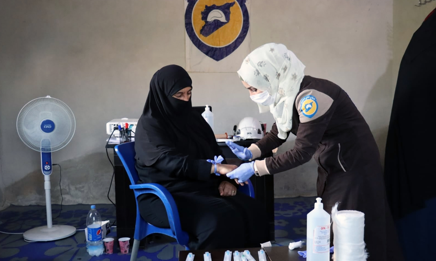 """A volunteer at the Syria Civil Defence Team (SCD) training """"Umm Mohammed"""" from the al-Ghab Plain during a course titled """"A Paramedic in Every Home"""" (Syria Civil Defence)"""