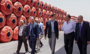 The head of the Syrian regime, Bashar al-Assad, along with some businessmen in the industrial city of Adra(SANA)